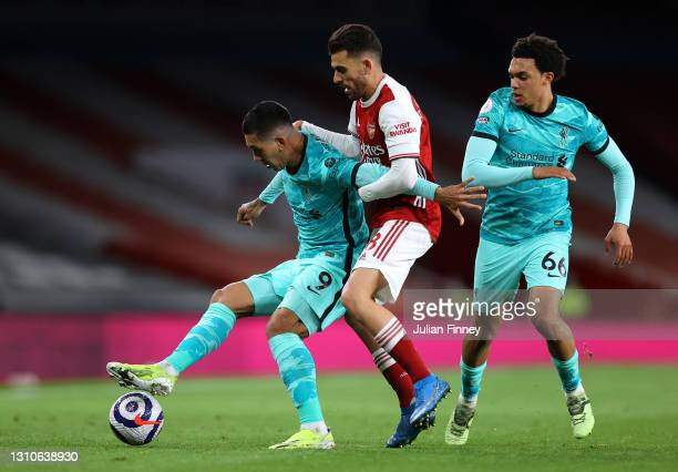 Roberto Firmino of Liverpool holds off Dani Ceballos of Arsenal as Trent Alexander-Arnold runs past during the Premier League match between Arsenal...