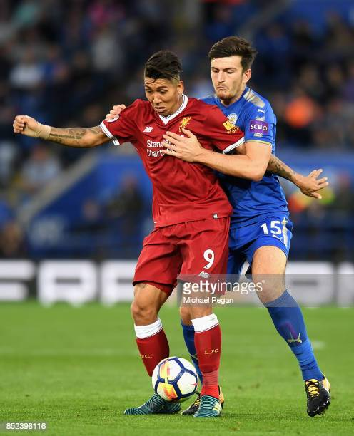 Roberto Firmino of Liverpool holds off Harry Maguire of Leicester City during the Premier League match between Leicester City and Liverpool at The...