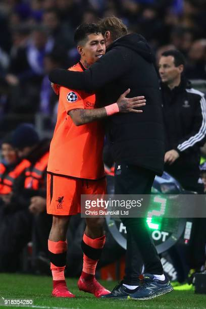 Roberto Firmino of Liverpool hugs Manager of Liverpool Jurgen Klopp after being substituted during the UEFA Champions League Round of 16 First Leg...