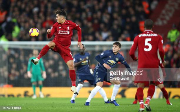 Roberto Firmino of Liverpool in action as Victor Lindelof of Manchester United looks on during the Premier League match between Liverpool FC and...