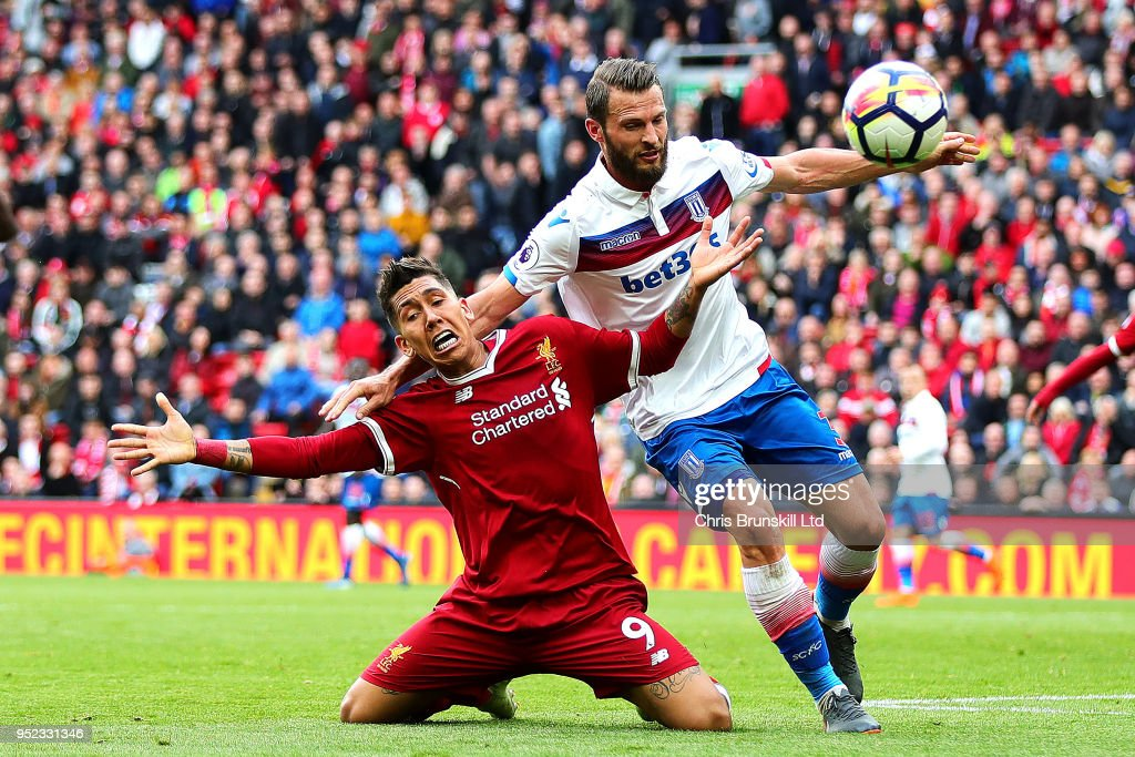Roberto Firmino of Liverpool in action with Erik Pieters of Stoke City during the Premier League match between Liverpool and Stoke City at Anfield on April 28, 2018 in Liverpool, England.