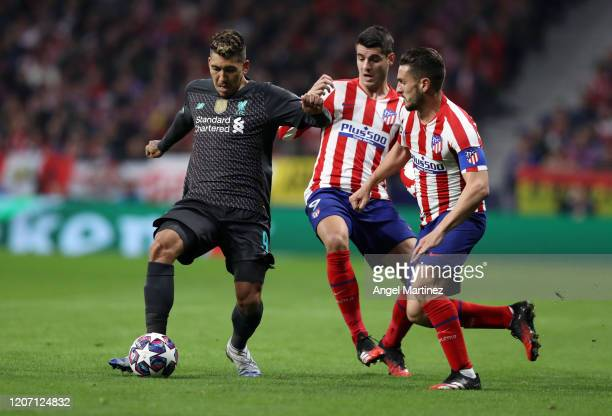Roberto Firmino of Liverpool is challenged by Alvaro Morata and Koke of Atletico Madrid during the UEFA Champions League round of 16 first leg match...