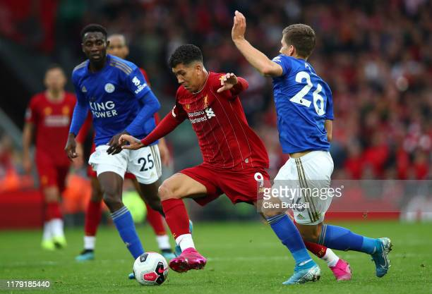 Roberto Firmino of Liverpool is challenged by Dennis Praet of Leicester City during the Premier League match between Liverpool FC and Leicester City...