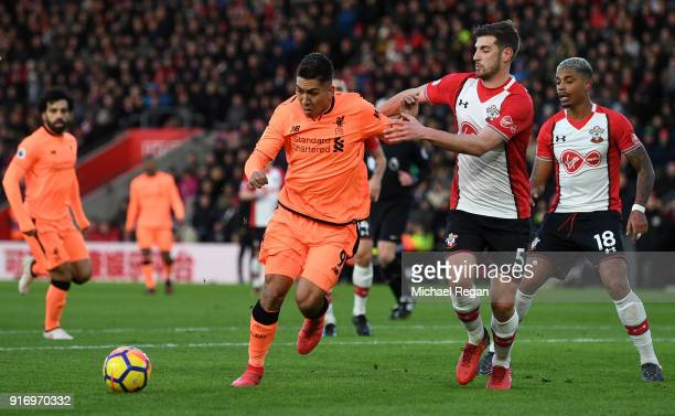 Roberto Firmino of Liverpool is challenged by Jack Stephens of Southampton during the Premier League match between Southampton and Liverpool at St...
