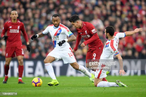 Roberto Firmino of Liverpool is challenged by Jordan Ayew and Luka Milivojevic of Crystal Palace during the Premier League match between Liverpool FC...