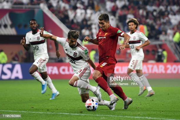 Roberto Firmino of Liverpool is challenged by Rodrigo Caio of CR Flamengo during the FIFA Club World Cup Qatar 2019 Final match between Liverpool FC...