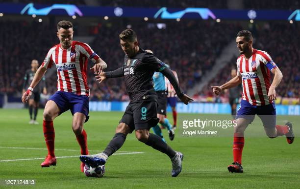 Roberto Firmino of Liverpool is challenged by Saul Niguez and Koke of Atletico Madrid during the UEFA Champions League round of 16 first leg match...