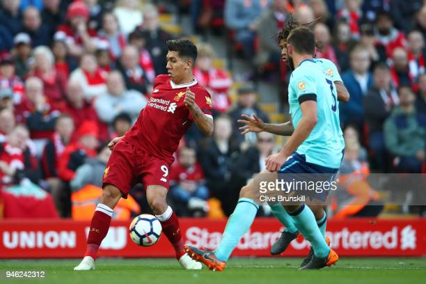 Roberto Firmino of Liverpool is challenged by the AFC Bournemouth defence during the Premier League match between Liverpool and AFC Bournemouth at...