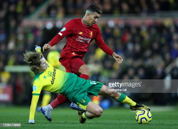 Roberto Firmino of Liverpool is challenged by Todd Cantwell of Norwich City during the Premier League match between Norwich City and Liverpool FC at...