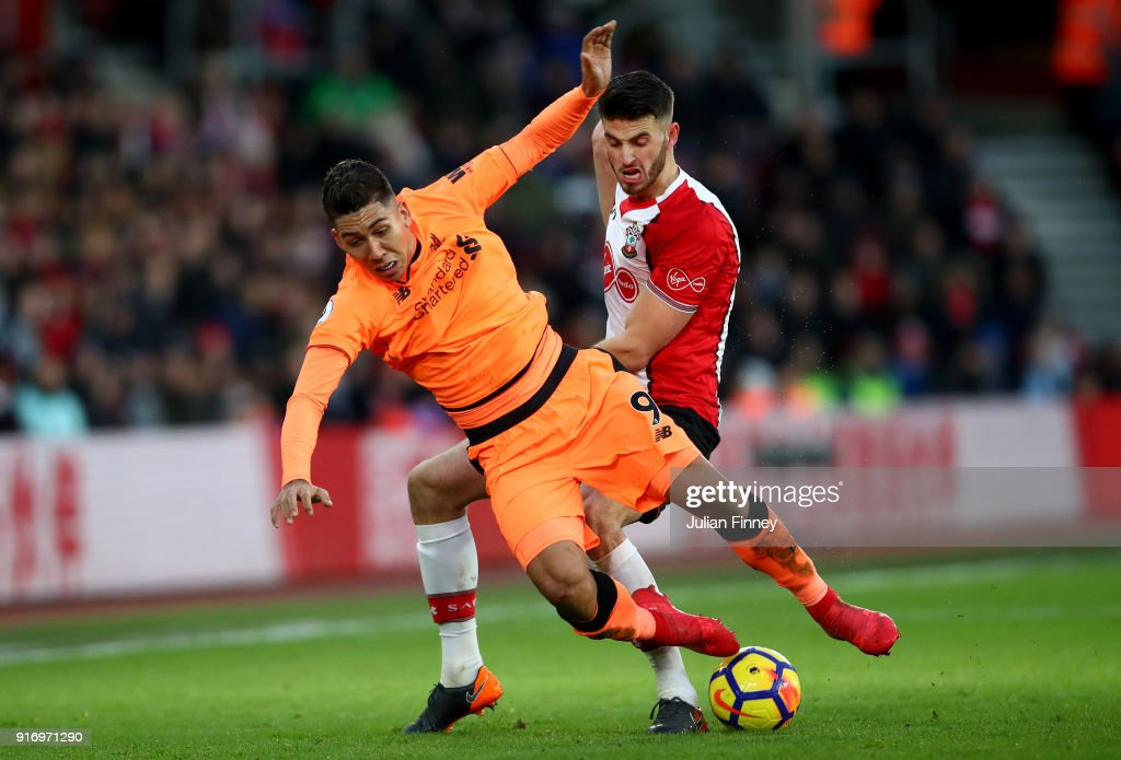 Roberto Firmino of Liverpool is challenged by Wesley Hoedt of Southampton during the Premier League match between Southampton and Liverpool at St Mary's Stadium on February 11, 2018 in Southampton, England.