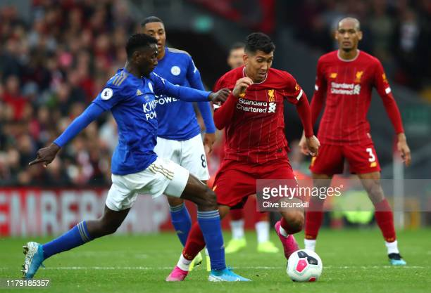 Roberto Firmino of Liverpool is challenged by Wilfred Ndidi of Leicester City during the Premier League match between Liverpool FC and Leicester City...