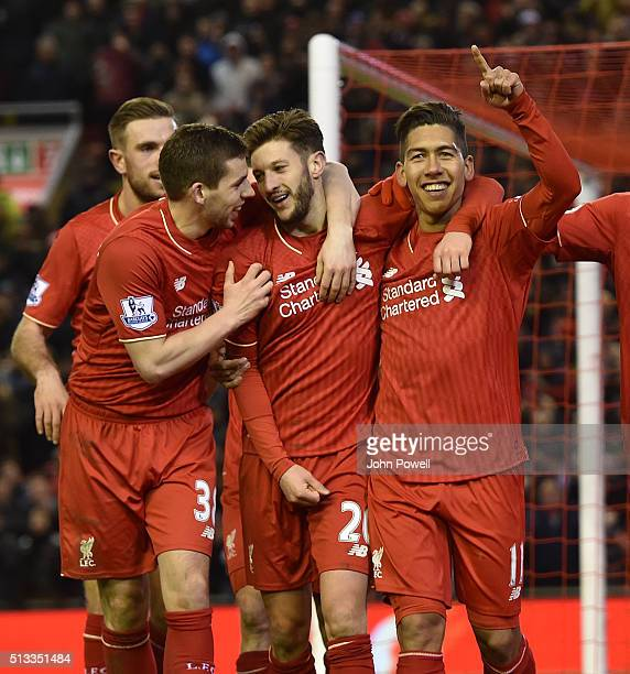 Roberto Firmino of Liverpool is congratulated after his goal during the Barclays Premier League match between Liverpool and Manchester City at...
