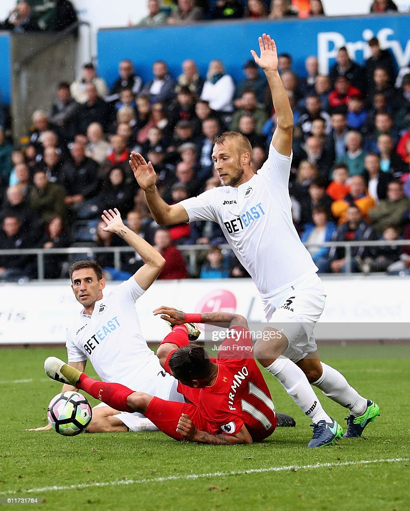 Roberto Firmino of Liverpool is fouled by Jordi Amat of Swansea City (L) and a penalty is awarded to Liverpool during the Premier League match between Swansea City and Liverpool at Liberty Stadium on October 1, 2016 in Swansea, Wales.
