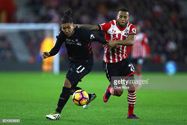 Roberto Firmino of Liverpool is pulled back by Ryan Bertrand of Southampton during the Premier League match between Southampton and Liverpool at St...