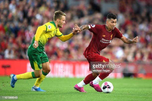 Roberto Firmino of Liverpool is tackled by Tom Trybull of Norwich City during the Premier League match between Liverpool FC and Norwich City at...