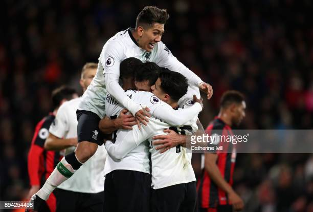 Roberto Firmino of Liverpool joins in Dejan Lovren's celebrations with his teammates after scoring his sides second goal during the Premier League...