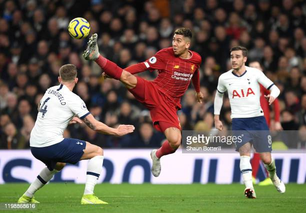 Roberto Firmino of Liverpool jumps for the ball against Toby Alderweireld of Tottenham Hotspur during the Premier League match between Tottenham...