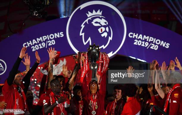 Roberto Firmino of Liverpool lifts The Premier League trophy following the Premier League match between Liverpool FC and Chelsea FC at Anfield on...