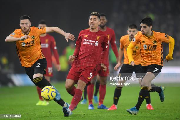 Roberto Firmino of Liverpool passes the ball undr pressure from Matt Doherty and Pedro Neto of Wolverhampton Wanderers during the Premier League...