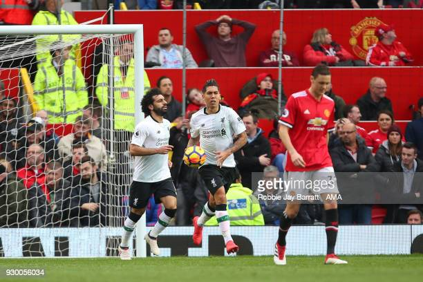 Roberto Firmino of Liverpool retrieves the ball after Eric Bailly of Manchester United scored an own goal to make it 2 1 during the Premier League...