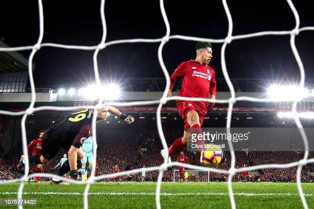 Roberto Firmino of Liverpool scores his sides first goal past Bernd Leno of Arsenal during the Premier League match between Liverpool FC and Arsenal...