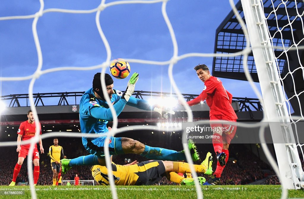 Roberto Firmino of Liverpool (R) scores his sides first goal past Petr Cech of Arsenal (L) during the Premier League match between Liverpool and Arsenal at Anfield on March 4, 2017 in Liverpool, England.
