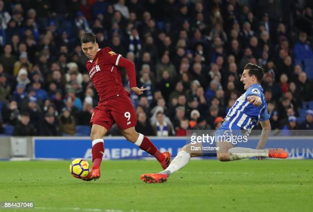 Roberto Firmino of Liverpool scores his sides third goal as Lewis Dunk of Brighton and Hove Albion attempts to block during the Premier League match...