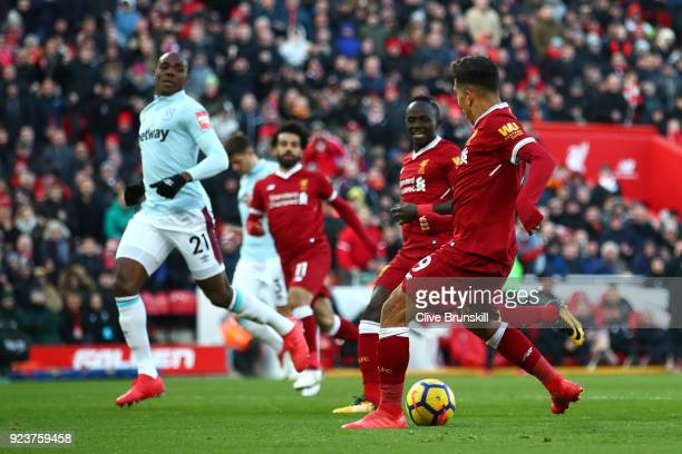 Roberto Firmino of Liverpool scores his side's third goal during the Premier League match between Liverpool and West Ham United at Anfield on...
