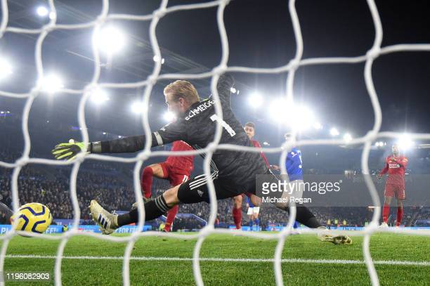 Roberto Firmino of Liverpool scores his team's first goal past Kasper Schmeichel of Leicester City during the Premier League match between Leicester...
