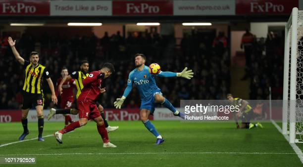 Roberto Firmino of Liverpool scores his team's third goal past Ben Foster of Watford during the Premier League match between Watford FC and Liverpool...