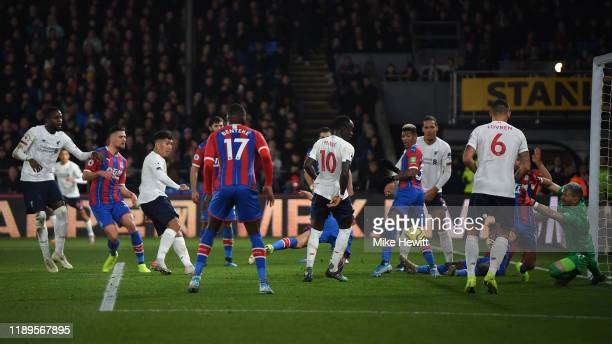 Roberto Firmino of Liverpool scores his team's winning goal despite the efforts of Vicente Guaita of Crystal Palace during the Premier League match...
