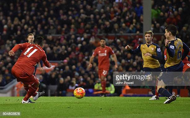 Roberto Firmino of Liverpool scores the first goal during the Barclays Premier League match between Liverpool and Arsenal at Anfield on January 13...