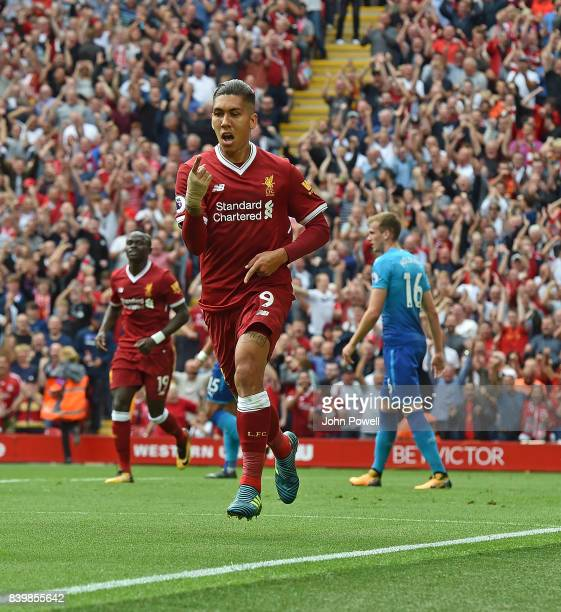 Roberto Firmino of Liverpool scores the opener and celebrates during the Premier League match between Liverpool and Arsenal at Anfield on August 27...