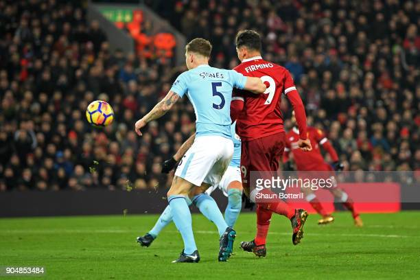 Roberto Firmino of Liverpool scores the second Liverpool goal past John Stones of Manchester City during the Premier League match between Liverpool...