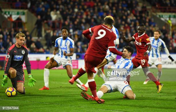 Roberto Firmino of Liverpool scores their second goal past goalkeeper Jonas Lossl of Huddersfield Town during the Premier League match between...