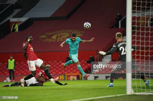 Roberto Firmino of Liverpool scores their side's second goal past Dean Henderson of Manchester United during the Premier League match between...