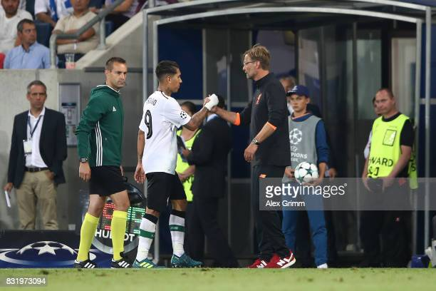 Roberto Firmino of Liverpool shakes hands with Juergen Klopp as he is substituted during the UEFA Champions League Qualifying PlayOffs Round First...