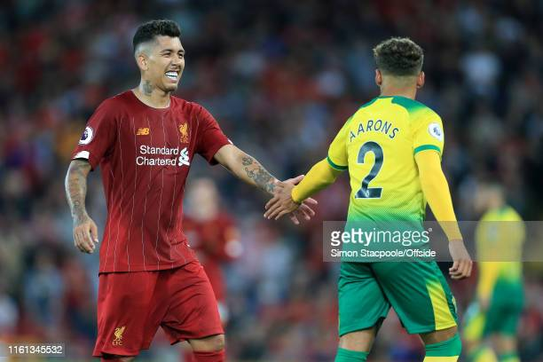 Roberto Firmino of Liverpool shakes hands with Max Aarons of Norwich during the Premier League match between Liverpool and Norwich City at Anfield on...