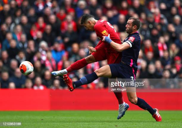 Roberto Firmino of Liverpool shoots while under pressure from Steve Cook of AFC Bournemouth during the Premier League match between Liverpool FC and...