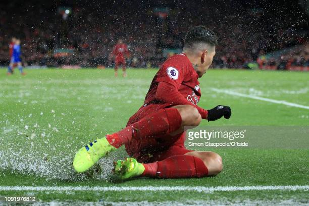 Roberto Firmino of Liverpool slides through the snow during the Premier League match between Liverpool and Leicester City at Anfield on January 30...