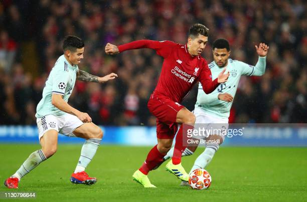 Roberto Firmino of Liverpool takes on James Rodriguez and Serge Gnabry of Bayern Munich during the UEFA Champions League Round of 16 First Leg match...