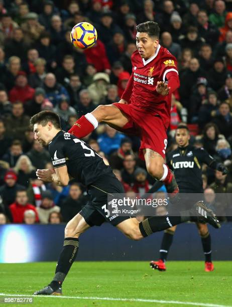 Roberto Firmino of Liverpool towers over Federico Fernandez of Swansea City to win the ball during the Premier League match between Liverpool and...