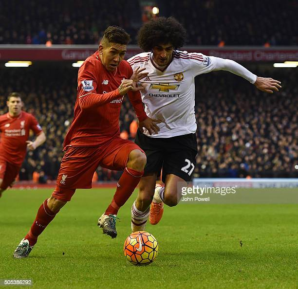 Roberto Firmino of Liverpool tussles with Marouane Fellaini of Manchester United during the Barclays Premier League match between Liverpool and...