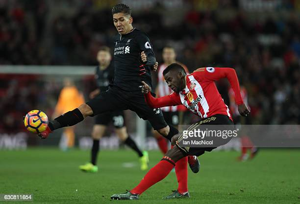 Roberto Firmino of Liverpool vies with Papy Djilobodji of Sunderland during the Premier League match between Sunderland and Liverpool at Stadium of...