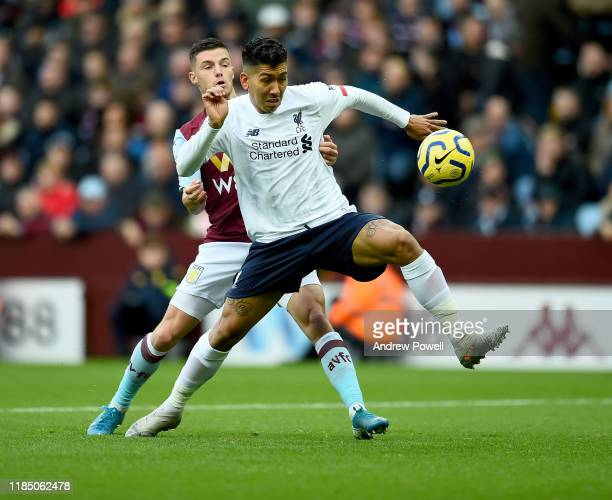Roberto Firmino of Liverpool with Frederic Guilbert of Aston Villa during the Premier League match between Aston Villa and Liverpool FC at Villa Park...