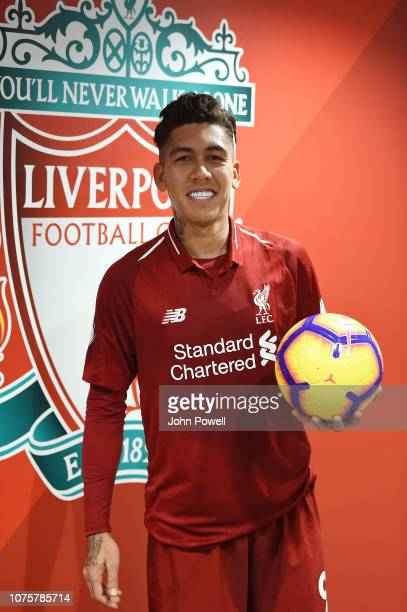 Roberto Firmino of Liverpool with his hat-trick ball at the end of the Premier League match between Liverpool FC and Arsenal FC at Anfield on...