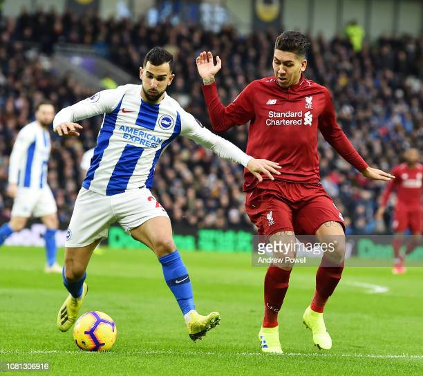Roberto Firmino of Liverpool with Martin Montoya of Brighton Hove Albion during the Premier League match between Brighton Hove Albion and Liverpool...