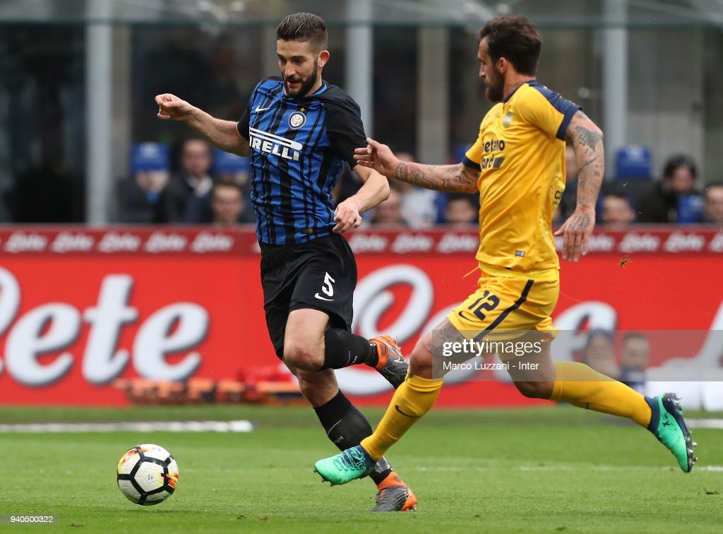 Roberto Gagliardini of FC Internazionale (L) competes for the ball with Antonio Caracciolo of Hellas Verona FC during the serie A match between FC Internazionale and Hellas Verona FC at Stadio Giuseppe Meazza on March 31, 2018 in Milan, Italy.
