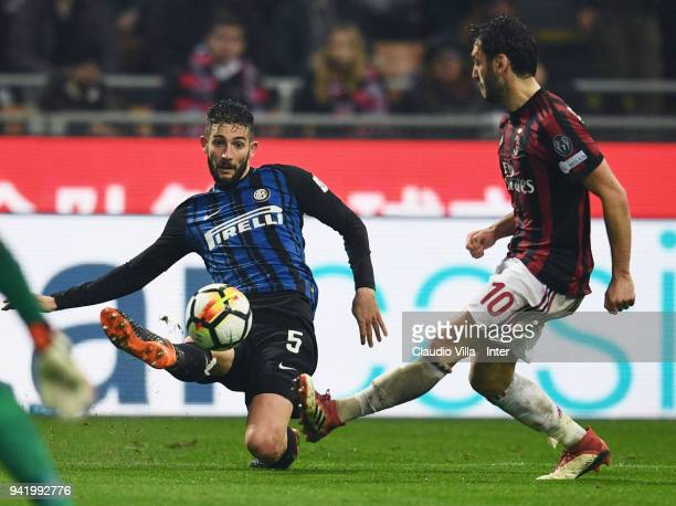 Roberto Gagliardini of FC Internazionale competes for the ball with Hakan Calhanoglu of AC Milan during the serie A match between AC Milan and FC...
