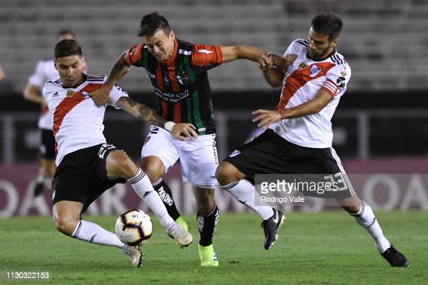 Roberto Gutierrez of Palestino fights for the ball with Leonardo Ponzio and Gonzalo Montiel of River Plate during a group A match between River Plate...